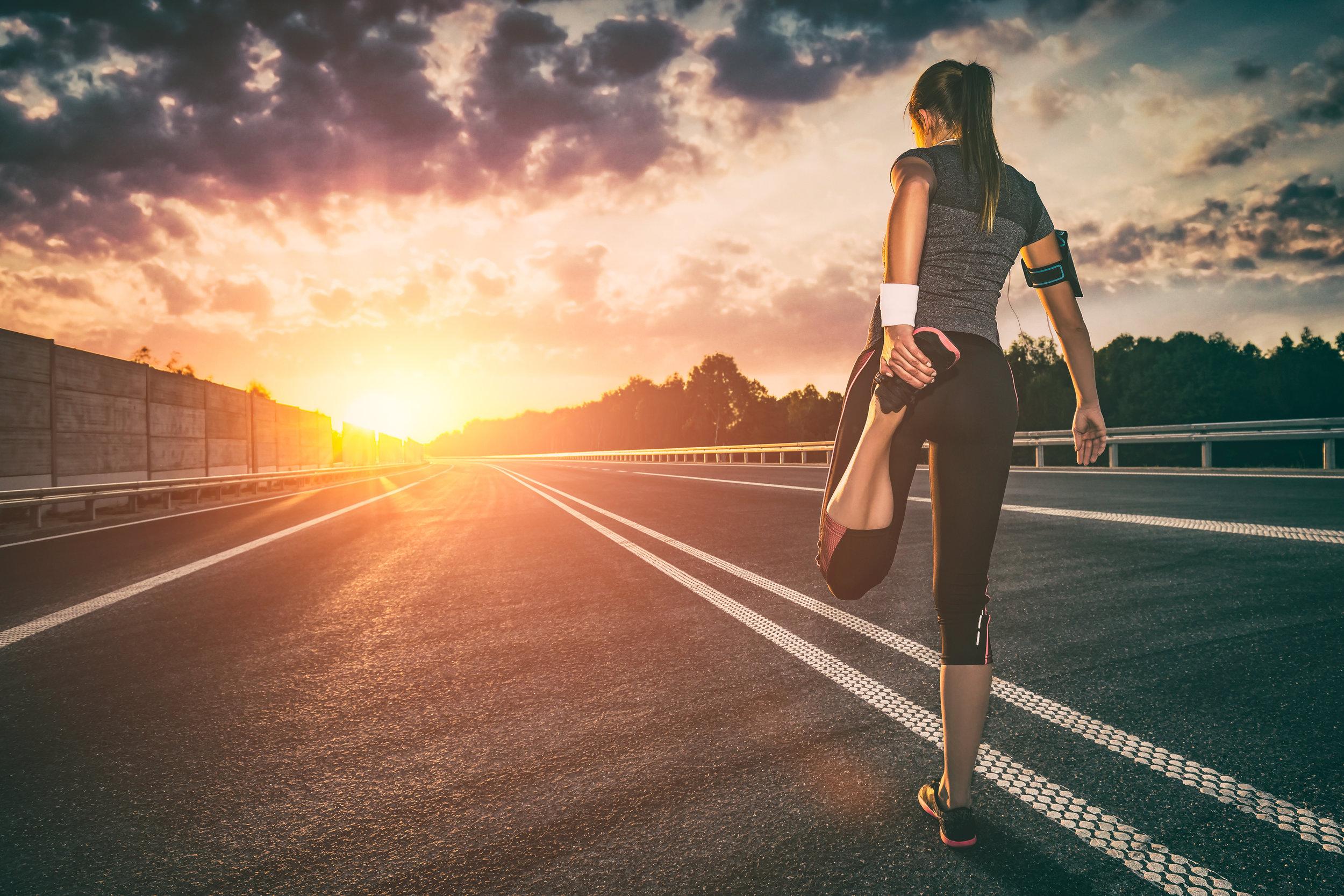 دونده در حال کشدن عضلات پا در جاده