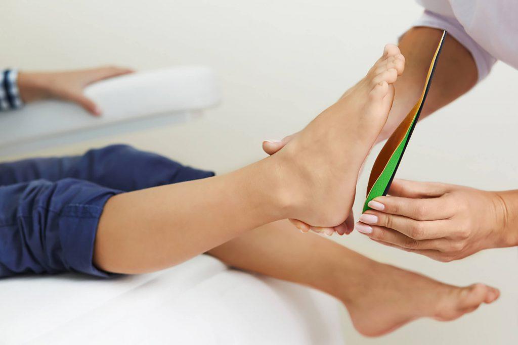 قرار دادن کفی طبی روی پای خانمی برای اصلاح کف پای صاف